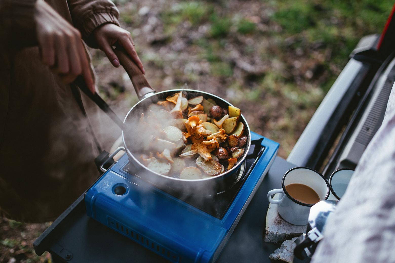 Eine Pilz-Kartoffel-Pfane wird im Kofferraum eines Autos auf einer mobilen Herdplatte gebraten.