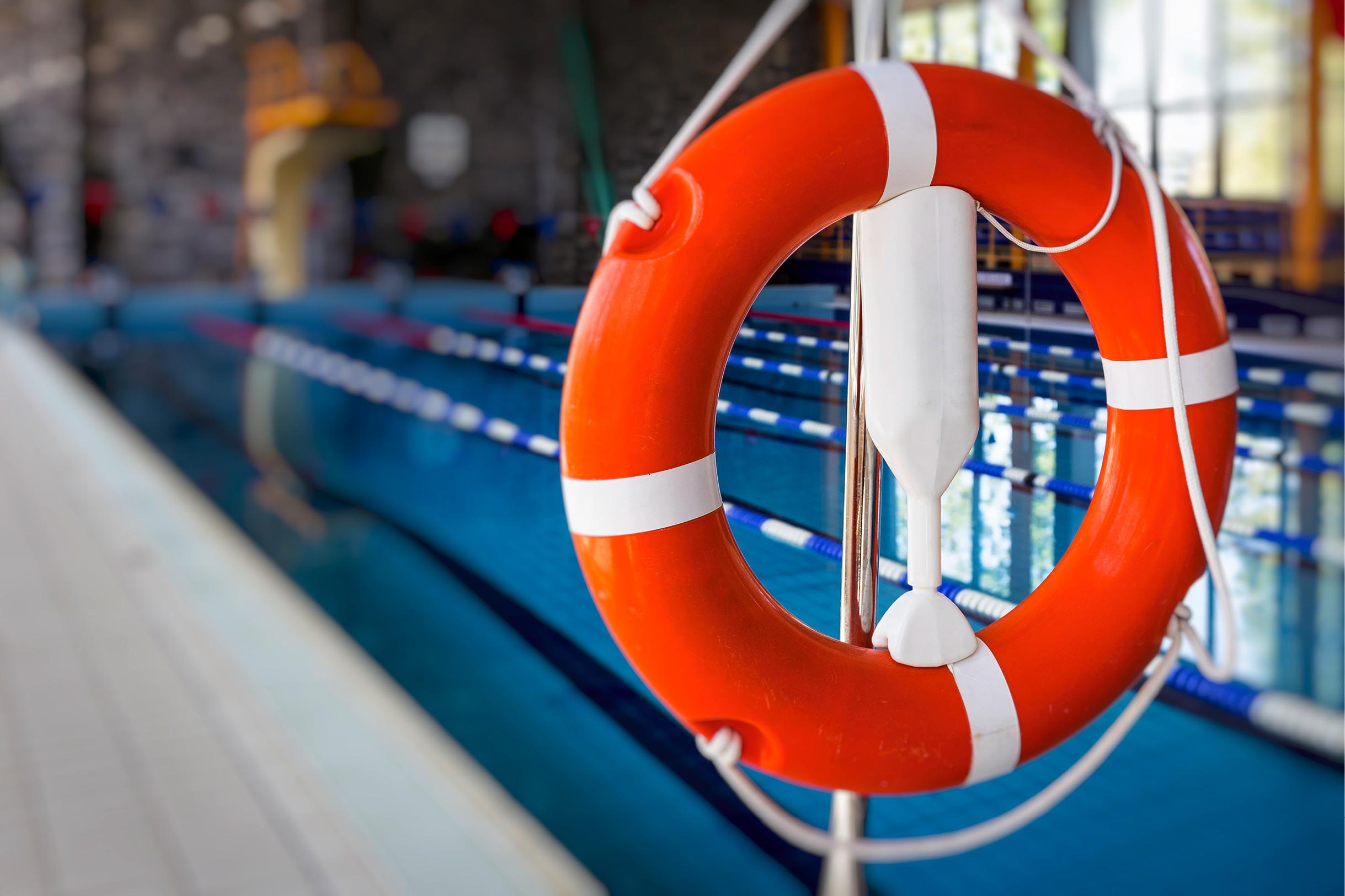 Ein Rettungsring hängt griffbereit am Rand eines Schwimmbeckens.