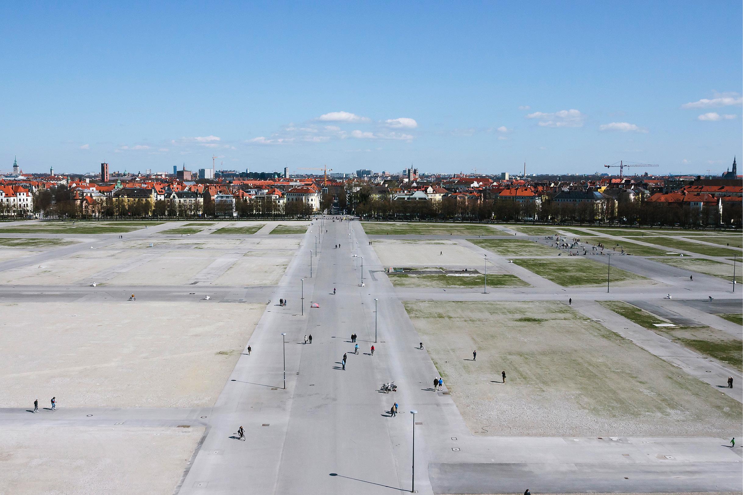 Einige Münchener spazieren über die leere Theresienwiese.